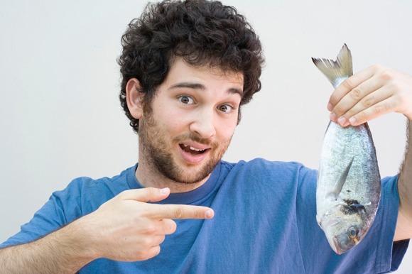 Hombre sujetando un pescado entero