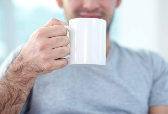 Hombre sosteniendo una taza de café con leche
