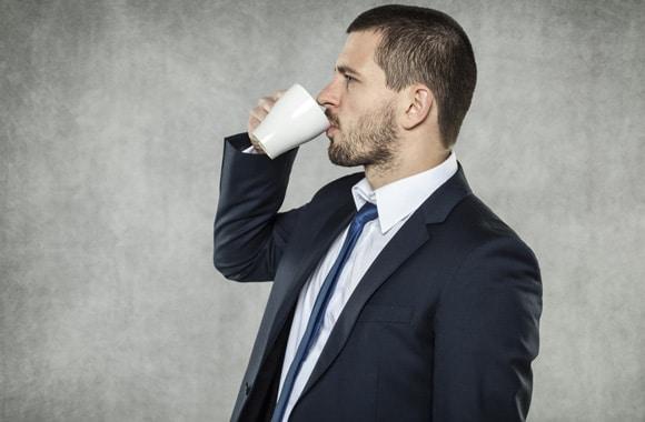 Hombre en traje tomando café