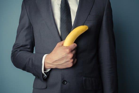 Hombre en traje sosteniendo un plátano