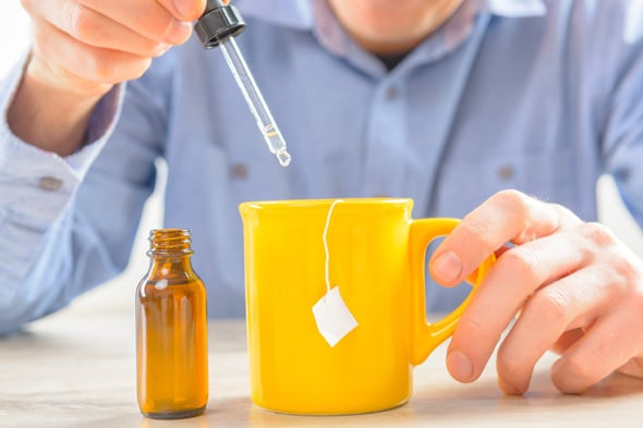 Hombre poniendo gotas de Stevia en té