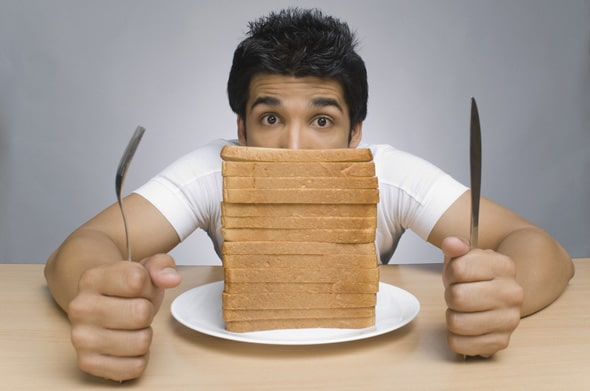 Hombre con una pila de rebanadas de pan