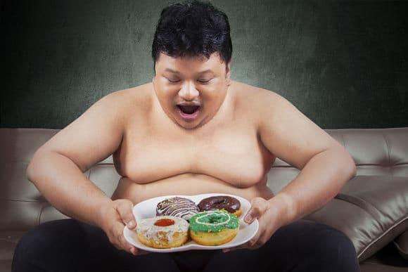 Hombre obeso mirando donas