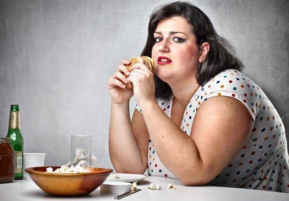 Mujer obesa comiendo comida chatarra