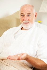 Anciano tomando pastillas