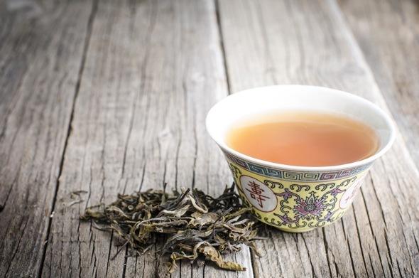 Hojas de té Oolong y té en una taza de té china