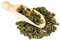 Hojas de té Oolong y cuchara de madera