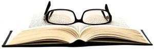 Libro abierto y gafas de lectura