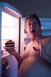 Hombre con sobrepeso comiendo pastel
