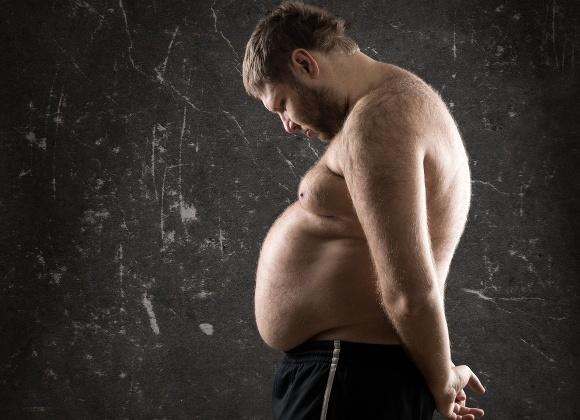 Hombre con sobrepeso mirando abatido