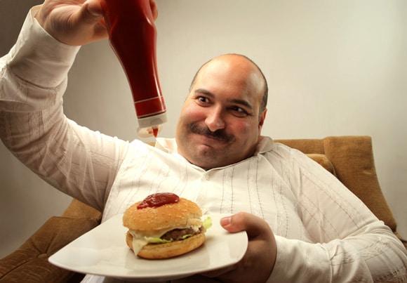 Hombre con sobrepeso vertiendo salsa de tomate en una hamburguesa