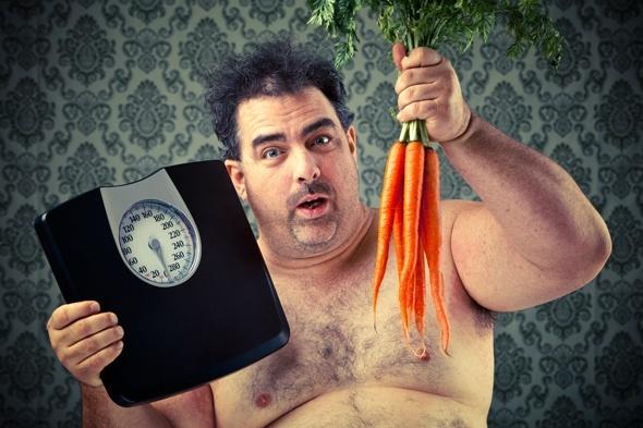 Hombre con sobrepeso con escala y zanahorias