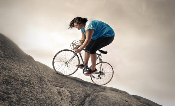 Mujer con sobrepeso en bicicleta por una pendiente empinada