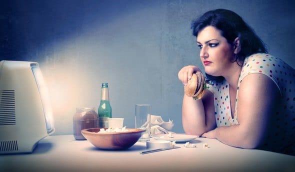 Mujer con sobrepeso comiendo delante de la televisión