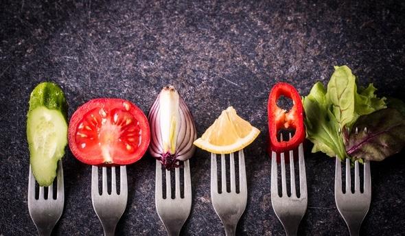 Seis tenedores con diferentes verduras y frutas en ellos