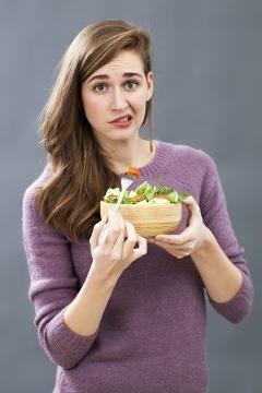 Mujer joven escéptica comiendo ensalada