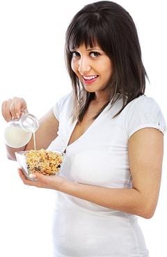 Morena sonriente vertiendo leche sobre cereales