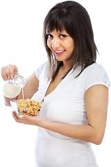 Sonriente morena vertiendo leche sobre cereales