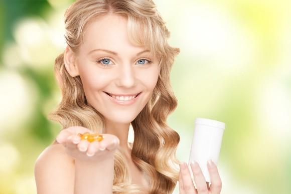 Mujer sonriente sosteniendo cápsulas de omega-3
