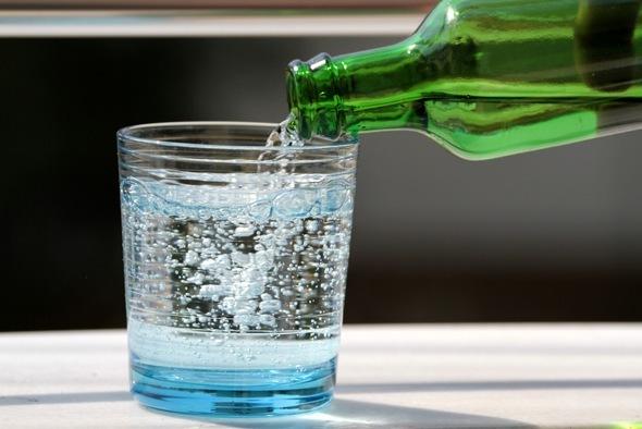 Verter agua con gas en un vaso