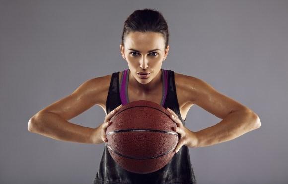 Mujer deportiva sosteniendo baloncesto