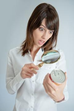 Mujer sorprendida examinando la etiqueta de los alimentos