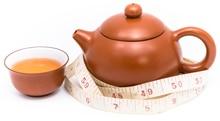 Tetera, taza de té y cinta métrica