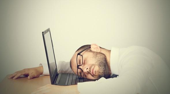 Hombre cansado durmiendo con la cabeza en su computadora portátil
