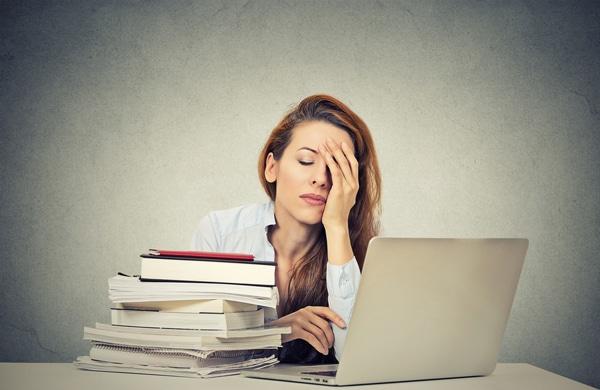 Mujer cansada sentada en su escritorio