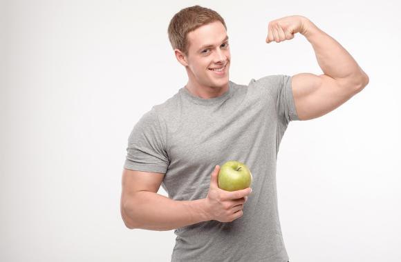 Hombre muy atlético flexionando sosteniendo manzana