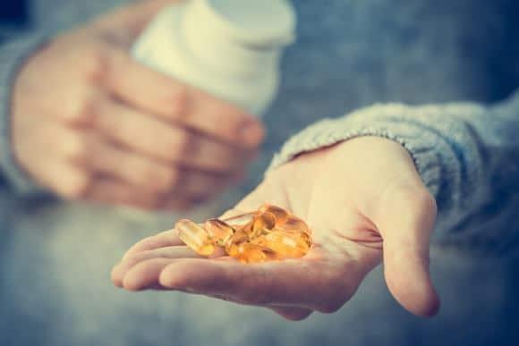 Cápsulas de vitamina D en la mano del hombre