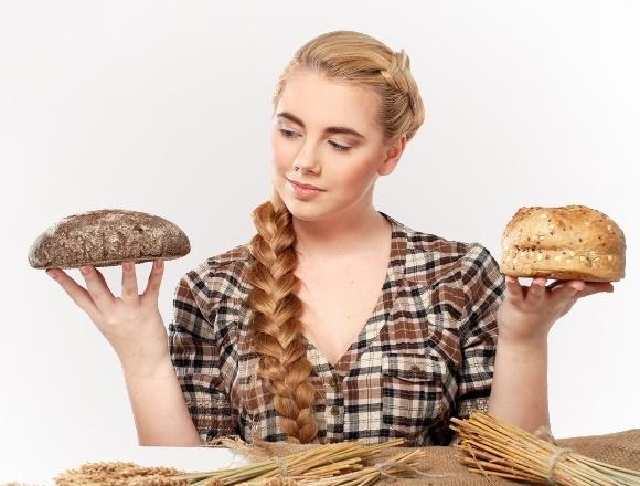 Mujer eligiendo entre pan de centeno y trigo
