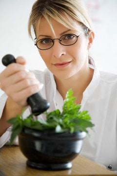 Mujer aplastando hojas de stevia
