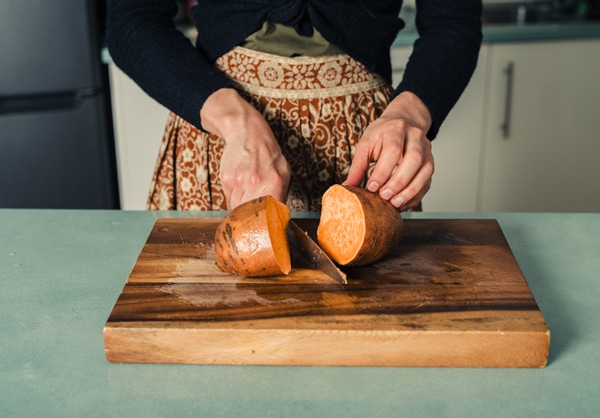 Mujer cortando una batata en una tabla de cortar
