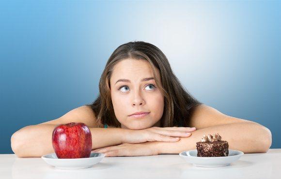 Mujer decidiendo entre manzana y pastel