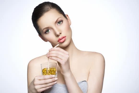 Mujer bebiendo pastillas con una pajita