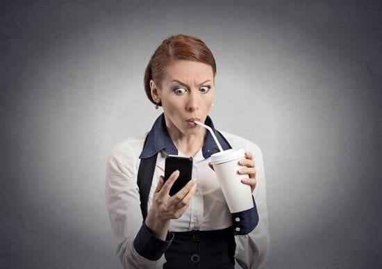 Mujer bebiendo refrescos mientras mira el teléfono