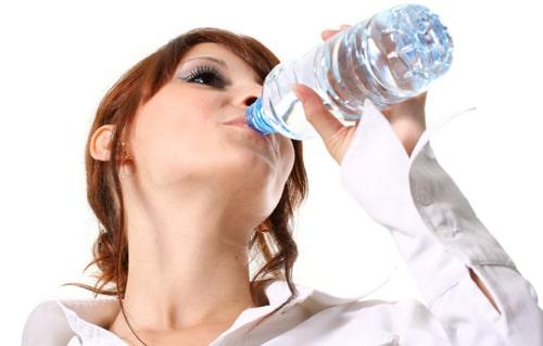 Mujer bebiendo agua de una botella