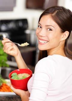 Mujer comiendo ensalada de quinua y brócoli