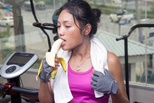 Mujer comiendo plátano en el gimnasio
