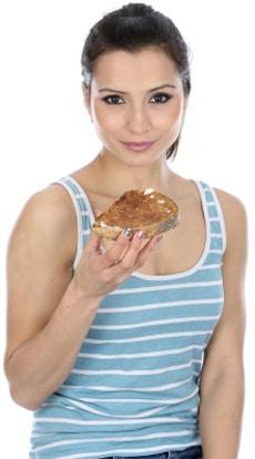 Mujer comiendo tostadas con mantequilla