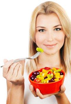 Mujer comiendo fruta de un tazón de fuente