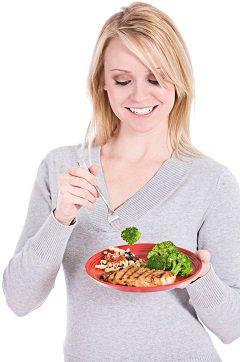 Mujer comiendo salmón y brócoli