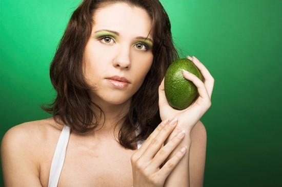 Mujer sosteniendo un aguacate verde, 550px
