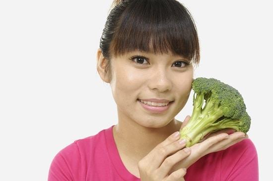 Mujer sosteniendo un trozo de brócoli