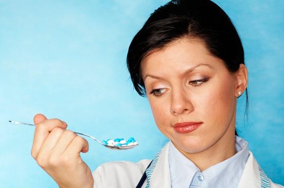 Mujer sosteniendo una cuchara llena de pastillas