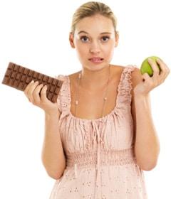 Mujer sosteniendo una manzana y chocolate