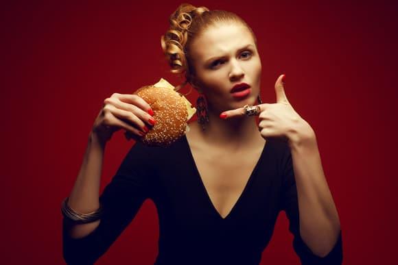 Mujer sosteniendo y apuntando a la hamburguesa