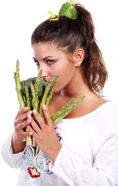 Mujer sosteniendo espárragos y brócoli