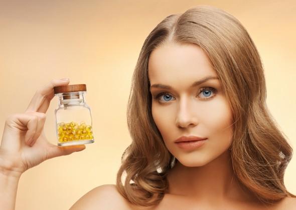 Mujer sosteniendo una botella de cápsulas llenas de aceite